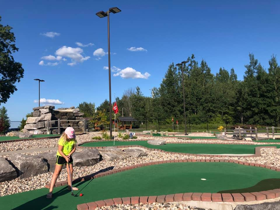 A girl is playing mini-golf in Blackbird Falls Mini Putt