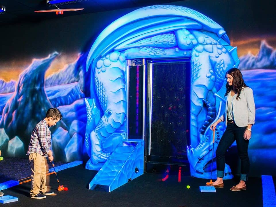 Mom and her son are playing mini putt in Dragon's Tale Blacklight Mini-Golf