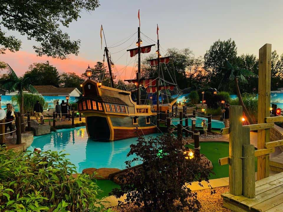 Mini golf fairways designed with a ship in the lake in Skull Island Miniature Golf