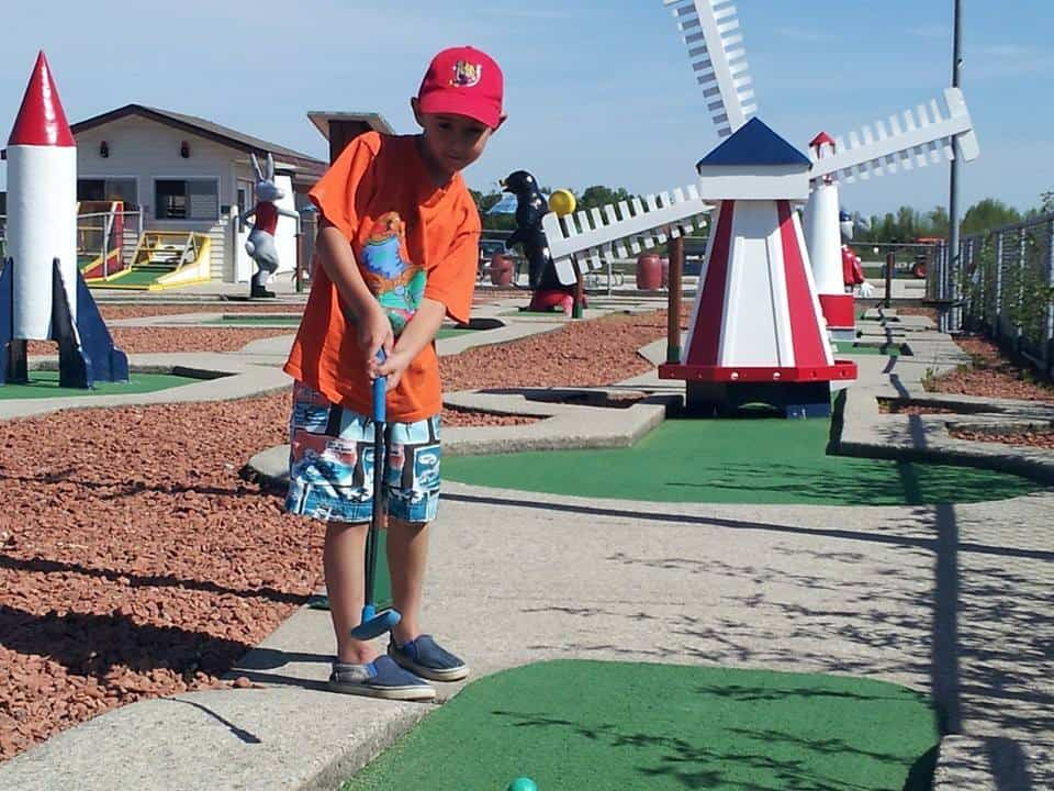 A boy is playing mini putt in Wasaga 500 Mini Golf club